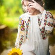 Young girl wearing Romanian traditional blouse holding a sunflower outdoor shot. Portrait of beautiful blonde girl with bright yellow flower. Beautiful woman looking at a flower harmony concept — Stock Photo #37812885