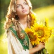Young girl wearing Romanian traditional blouse holding sunflowers outdoor shot. Portrait of beautiful blonde girl with bright yellow flowers bouquet. Beautiful woman with long fair hair - fairy look — Stock Photo #37812893