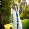 Young woman wearing a long white dress holding a sunflower outdoor shot. Portrait of beautiful blonde girl with bright yellow flower in forest. Attractive girl with long hair - fairy tale scenery — Stock Photo
