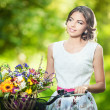 Beautiful girl wearing a nice white dress having fun in park with bicycle carrying a beautiful basket full of flowers. Vintage scenery. Pretty blonde girl with retro look, bike and basket with flowers — Stock Photo #37812923