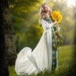 Young woman wearing a long white dress holding sunflowers outdoor shot. Portrait of beautiful blonde girl with bright yellow flowers bouquet. Attractive girl with long hair - fairy tale scenery — Stock Photo