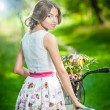 Beautiful girl wearing a nice white dress having fun in park with bicycle. Healthy outdoor lifestyle concept. Vintage scenery. Pretty blonde girl with retro look with bike and basket with flowers — Stock Photo #37812935