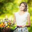 Photo: Beautiful girl wearing nice white dress having fun in park with bicycle carrying beautiful basket full of flowers. Vintage scenery. Pretty blonde girl with retro look, bike and basket with flowers