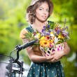 Beautiful girl with cute hat and basket with flowers having fun in park with bicycle. Healthy outdoor lifestyle concept. Vintage scenery. Pretty blonde girl with retro look with bike — Stock Photo