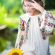 Young girl wearing Romanian traditional blouse holding a sunflower outdoor shot. Portrait of beautiful blonde girl with bright yellow flower. Beautiful woman looking at a flower harmony concept — Stock Photo