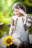 Young girl wearing Romanian traditional blouse holding a sunflower outdoor shot. Portrait of beautiful blonde girl with bright yellow flower. Beautiful woman looking at a flower harmony concept — Zdjęcie stockowe