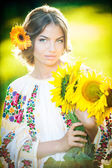 Young girl wearing Romanian traditional blouse holding sunflowers outdoor shot. Portrait of beautiful blonde girl with bright yellow flowers bouquet. Beautiful woman with yellow flower in hair posing — Zdjęcie stockowe