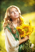 Young girl wearing Romanian traditional blouse holding sunflowers outdoor shot. Portrait of beautiful blonde girl with bright yellow flowers bouquet. Beautiful woman with long fair hair - fairy look — Stock Photo