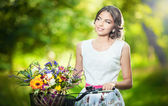 Beautiful girl wearing a nice white dress having fun in park with bicycle carrying a beautiful basket full of flowers. Vintage scenery. Pretty blonde girl with retro look, bike and basket with flowers — Stock Photo