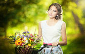 Beautiful girl wearing a nice white dress having fun in park with bicycle carrying a beautiful basket full of flowers. Vintage scenery. Pretty blonde girl with retro look, bike and basket with flowers — Stok fotoğraf