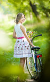Beautiful girl wearing a nice white dress having fun in park with bicycle. Healthy outdoor lifestyle concept. Vintage scenery. Pretty blonde girl with retro look with bike and basket with flowers — Stock Photo