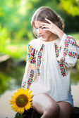 Young girl wearing Romanian traditional blouse holding a sunflower outdoor shot. Portrait of beautiful blonde girl with bright yellow flower. Beautiful woman looking at a flower harmony concept — Стоковое фото