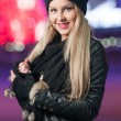 Fashionable lady wearing cap and black jacket outdoor in xmas scenery with blue lights in background. Portrait of young beautiful woman with long fair hair posing smiling in winter style. — Stock Photo #37844663