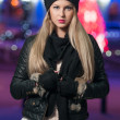 Fashionable lady wearing cap and black jacket outdoor in xmas scenery with blue lights in background. Portrait of young beautiful woman with long fair hair posing smiling in winter style. — Stock Photo #37844675