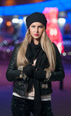 Fashionable lady wearing cap and black jacket outdoor in xmas scenery with blue lights in background. Portrait of young beautiful woman with long fair hair posing smiling in winter style. — Stock Photo
