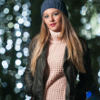 Fashionable lady wearing cap and black jacket outdoor in xmas scenery with blue lights in background. Portrait of young beautiful woman with long fair hair posing smiling in winter style. — Stock Photo #37863119