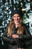 Fashionable lady wearing cap and black jacket outdoor in xmas scenery with blue lights in background. Portrait of young beautiful woman with long fair hair posing smiling in winter style. — Stockfoto