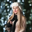 Fashionable lady wearing white fur cap and black muffler outdoor in Xmas scenery with blue lights in background. Portrait of young beautiful woman with long fair hair posing smiling in winter style. — Стоковое фото #37901583