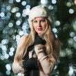 Fashionable lady wearing white fur cap and black muffler outdoor in Xmas scenery with blue lights in background. Portrait of young beautiful woman with long fair hair posing smiling in winter style. — Stok fotoğraf #37901585