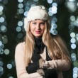 Fashionable lady wearing white fur cap and black muffler outdoor in Xmas scenery with blue lights in background. Portrait of young beautiful woman with long fair hair posing smiling in winter style. — Foto de Stock   #37901587