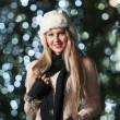 Fashionable lady wearing white fur cap and black muffler outdoor in Xmas scenery with blue lights in background. Portrait of young beautiful woman with long fair hair posing smiling in winter style. — Стоковое фото #37901589