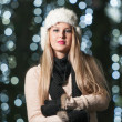 Fashionable lady wearing white fur cap and black muffler outdoor in Xmas scenery with blue lights in background. Portrait of young beautiful woman with long fair hair posing smiling in winter style. — Stok fotoğraf #37901595