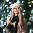 Fashionable lady wearing white fur cap and black muffler outdoor in Xmas scenery with blue lights in background. Portrait of young beautiful woman with long fair hair posing smiling in winter style. — Стоковое фото #37901605