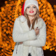 Fashionable lady wearing Xmas hat and white fur coat outdoor. Portrait of young beautiful woman in winter style. Bright picture of beautiful blonde woman with make up wearing Santa hat — Stock Photo #38166401