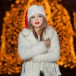 Fashionable lady wearing Xmas hat and white fur coat outdoor. Portrait of young beautiful woman in winter style. Bright picture of beautiful blonde woman with make up wearing Santa hat — Stock Photo #38166403