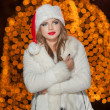 Fashionable lady wearing Xmas hat and white fur coat outdoor. Portrait of young beautiful woman in winter style. Bright picture of beautiful blonde woman with make up wearing Santa hat — Stock Photo