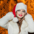 Fashionable lady wearing Xmas hat and white fur coat outdoor. Portrait of young beautiful woman in winter style. Bright picture of beautiful blonde woman with make up wearing Santa hat — Zdjęcie stockowe