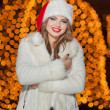 Fashionable lady wearing Xmas hat and white fur coat outdoor. Portrait of young beautiful woman in winter style. Bright picture of beautiful blonde woman with make up wearing Santa hat — Stockfoto