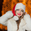 Fashionable lady wearing Xmas hat and white fur coat outdoor. Portrait of young beautiful woman in winter style. Bright picture of beautiful blonde woman with make up wearing Santa hat — Foto Stock