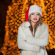 Fashionable lady wearing Xmas hat and white fur coat outdoor. Portrait of young beautiful woman in winter style. Bright picture of beautiful blonde woman with make up wearing Santa hat — Stock Photo #38166427
