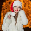 Fashionable lady wearing Xmas hat and white fur coat outdoor. Portrait of young beautiful woman in winter style. Bright picture of beautiful blonde woman with make up wearing Santa hat — Stock Photo #38166429