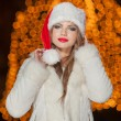 Fashionable lady wearing Xmas hat and white fur coat outdoor. Portrait of young beautiful woman in winter style. Bright picture of beautiful blonde woman with make up wearing Santa hat — Foto de Stock