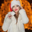 Fashionable lady wearing Xmas hat and white fur coat outdoor. Portrait of young beautiful woman in winter style. Bright picture of beautiful blonde woman with make up wearing Santa hat — Stock Photo #38166433