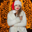 Fashionable lady wearing Xmas hat and white fur coat outdoor. Portrait of young beautiful woman in winter style. Bright picture of beautiful blonde woman with make up wearing Santa hat — Stock Photo #38166435