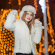 Fashionable lady wearing white fur accessories outdoor with bright Xmas lights in background. Portrait of young beautiful woman in winter style. Bright picture of beautiful blonde woman with make up — Stock Photo #38216709