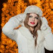 Fashionable lady wearing white fur accessories outdoor with bright Xmas lights in background. Portrait of young beautiful woman in winter style. Bright picture of beautiful blonde woman with make up — Stock Photo #38216725