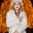 Fashionable lady wearing white fur cap and coat outdoor with bright Xmas lights in background. Portrait of young beautiful woman in winter style. Bright picture of beautiful blonde woman with make up — Stock Photo #38216729