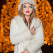 Fashionable lady wearing white fur cap and coat outdoor with bright Xmas lights in background. Portrait of young beautiful woman in winter style. Bright picture of beautiful blonde woman with make up — Stock Photo