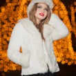 Fashionable lady wearing white fur cap and coat outdoor with bright Xmas lights in background. Portrait of young beautiful woman in winter style. Bright picture of beautiful blonde woman with make up — Stock Photo #38216731