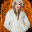 Fashionable lady wearing white fur cap and coat outdoor with bright Xmas lights in background. Portrait of young beautiful woman in winter style. Bright picture of beautiful blonde woman with make up — Stock Photo #38216733