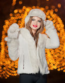Fashionable lady wearing white fur accessories outdoor with bright Xmas lights in background. Portrait of young beautiful woman in winter style. Bright picture of beautiful blonde woman with make up — Stock Photo
