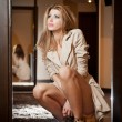 Portrait of blonde woman wearing a coat indoor. Beautiful young woman in coat posing in modern interior. Woman in casual style coat and high heels animal print boots thinking. Full body shoot indoor — Foto de Stock