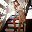 Full-length portrait of blonde woman wearing a coat posing provocatively on steps in a modern interior. Beautiful woman in casual style coat and high heel shoes on stairs full body shoot indoor — Stock Photo #38313255