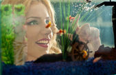 Beautiful blonde girl looking at golden fishes in aquarium. Attractive female with gorgeous smile admiring a large aquarium. Pretty woman playing with colored fishes swimming in aquarium — Stock Photo