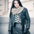 Attractive young woman in a winter fashion shot. Beautiful fashionable young girl in black leather outfit posing outdoor. Elegant long hair brunette with handbag and scarf in urban scenery. — Stock Photo
