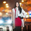 Fashionable lady wearing red dress and white coat outdoor in urban scenery with city lights in background. Full length portrait of young beautiful elegant woman posing in winter style. Street shot. — Zdjęcie stockowe #38589703